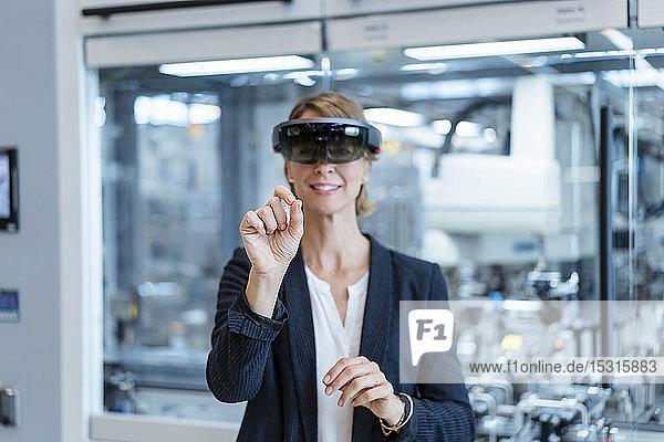 Geschäftsfrau mit AR-Brille in einer modernen Fabrik