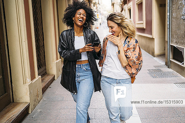 Multicultural happy women walking in the city  looking on smartphone and laughing