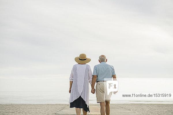 Rückenansicht eines älteren Ehepaares  das Hand in Hand auf einer Holzpromenade steht und aufs Meer blickt  Liepaja  Lettland