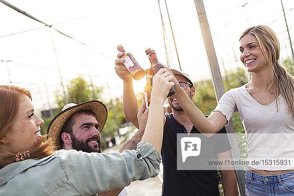 Gruppe von Freunden stößt mit Bierflaschen im Gewächshaus an