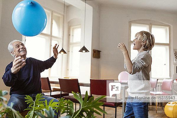 Glücklicher Großvater und Enkel spielen zu Hause mit dem Ballon