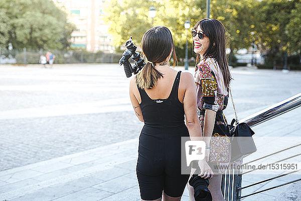 Fotograf und glückliches Modell unterhalten sich im Freien