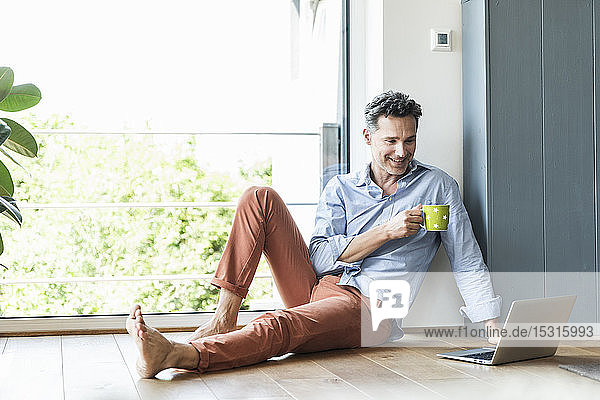 Mature man relaxing at home with a cup of coffee  using laptop