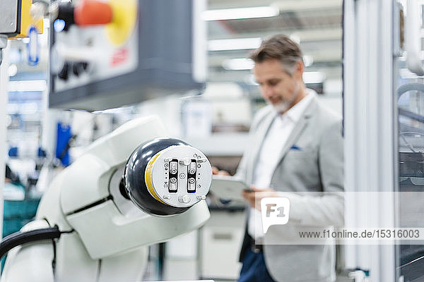 Businessman with tablet at assembly robot in a factory