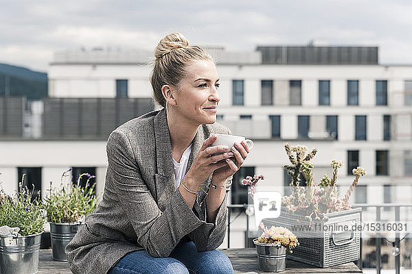 Businesswoman with coffee cup sitting on roof terrace having a break