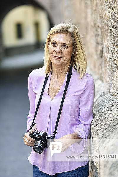Mature woman with a SLR camera in the city