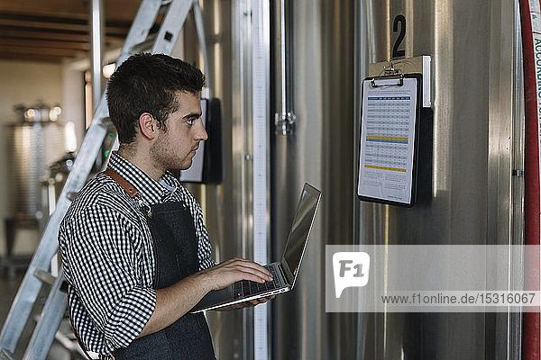 Jungunternehmer arbeitet mit Laptop in einer Brauerei