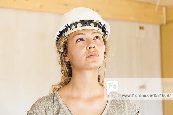 Junge Frau prüft den Bau eines neuen Holzhauses Junge Frau prüft den Bau eines neuen Holzhauses