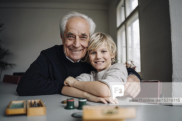 Portrait of happy watchmaker and his grandson sitting at table