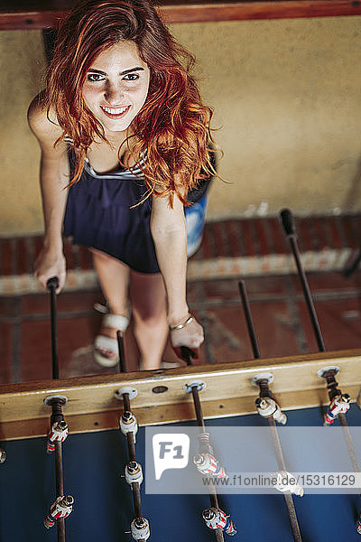 Portrait of happy young woman playing foosball in a sports bar