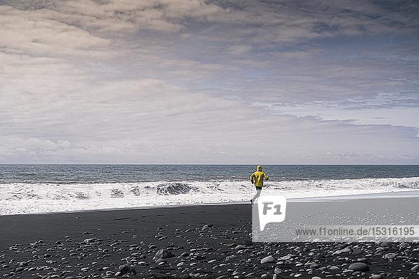 Erwachsener Mann rennt an einem Lavastrand in Island