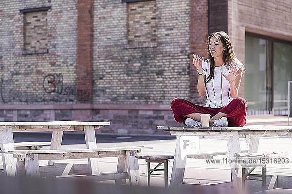 Junge Frau  die in einem Biergarten am Tisch sitzt und telefoniert