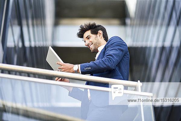 Lächelnder Geschäftsmann benutzt Tablette auf dem Balkon eines Bürogebäudes