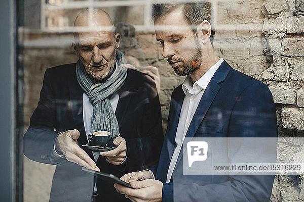 Älterer und mittel-erwachsener Geschäftsmann teilen sich eine Tablette