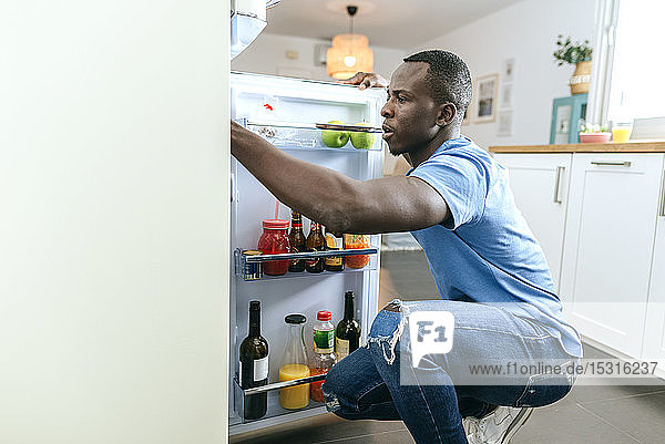 Junger Mann schaut zu Hause in den Kühlschrank in der Küche