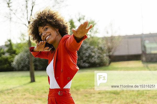 Porträt einer lachenden jungen Frau in einem modischen roten Hosenanzug