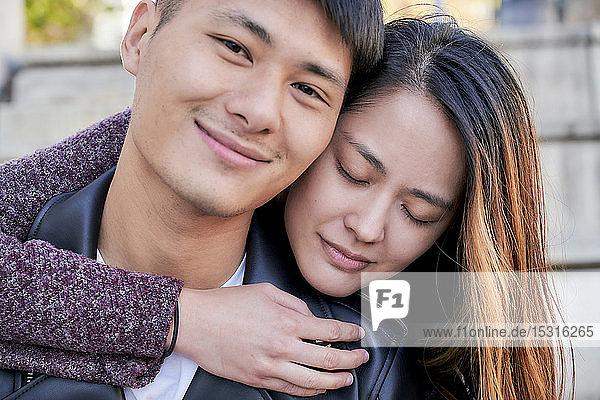 Glückliche junge Frau umarmt Freund im Freien