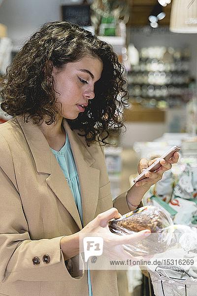 Junge Frau kauft in einem Lebensmittelgeschäft ein und benutzt ein Smartphone