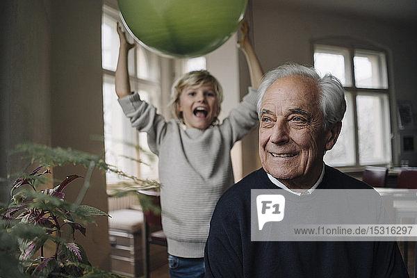 Porträt eines lächelnden älteren Mannes mit Enkel  der im Hintergrund einen Ballon hält