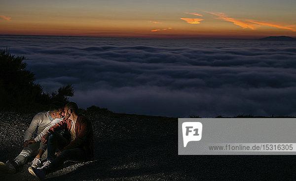 Schwules Paar küsst sich bei Sonnenuntergang in den Bergen über den Wolken
