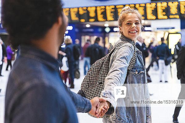 Porträt einer glücklichen jungen Frau Hand in Hand mit seinem Freund am Bahnhof
