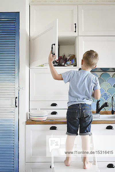 Back view of little boy standing on chair in the kitchen looking into cupboard