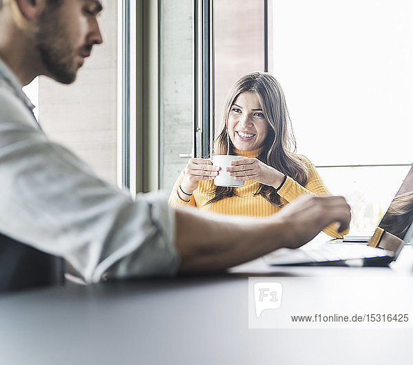 Young businesswoman and businessman sitting at desk in office talking