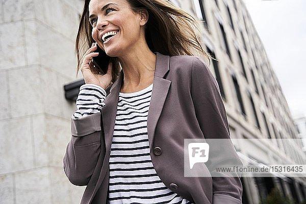 Glückliche Geschäftsfrau am Telefon in der Stadt