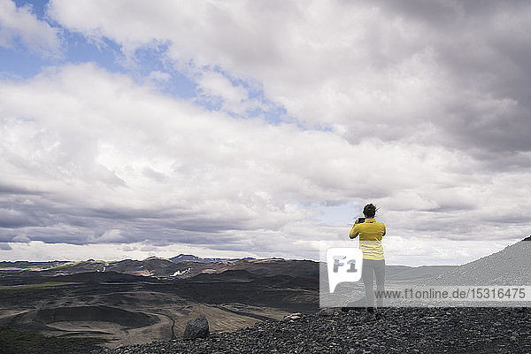 Young woman standing on Hverfjall crater near Myvatn  Iceland  looking at view