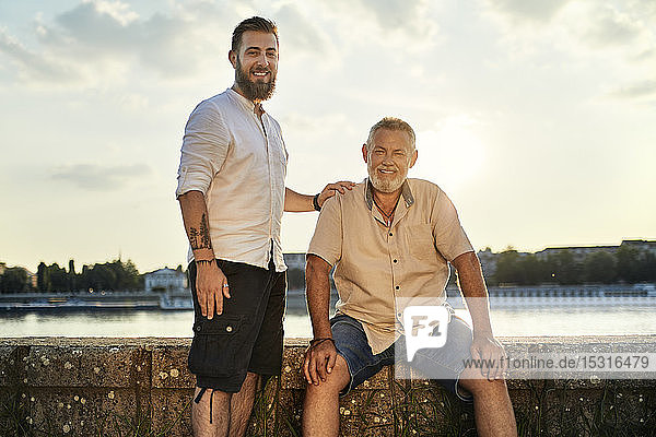 Portrait of smiling father and adult son at the riverside at sunset
