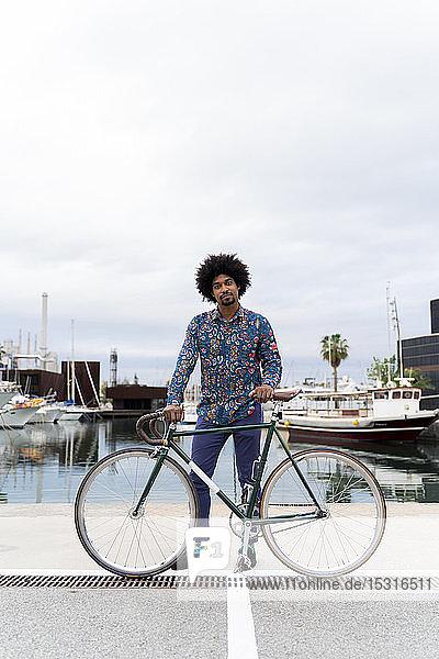 Porträt eines stilvollen Mannes mit Fahrrad am Yachthafen