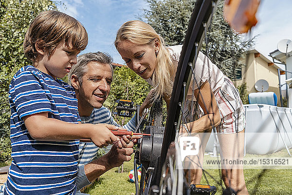 Family repairing a bicycle together in garden