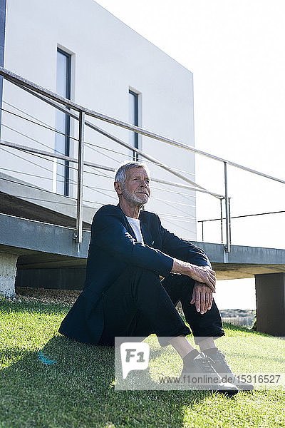 Senior businessman sitting on lawn outside a building