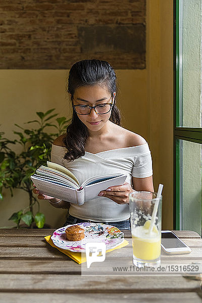Young woman sitting at table reading a book