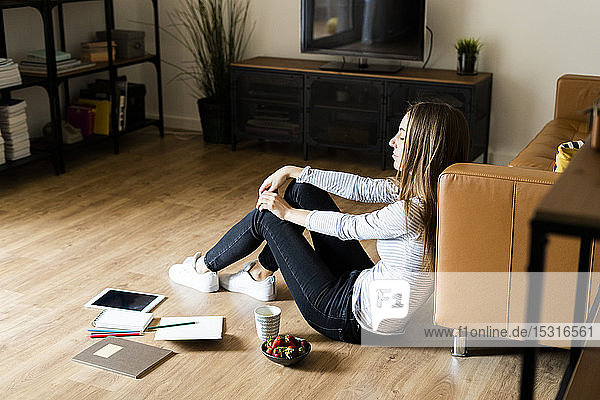 Relaxed young woman sitting on the floor at home having a break