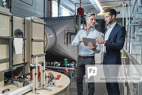Zwei Geschäftsleute mit Tablette im Gespräch in einer modernen Fabrik