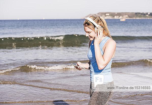 Joggerin am Strand  mit Smartphone und Kopfhörern
