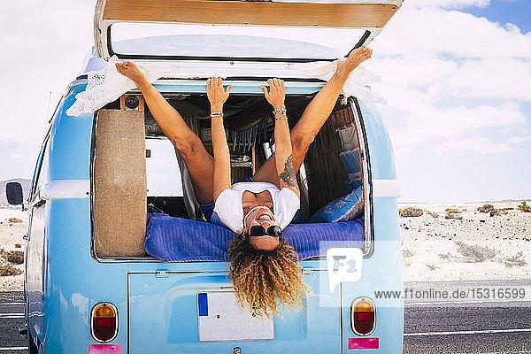 Lächelnde Frau im Lieferwagen liegend