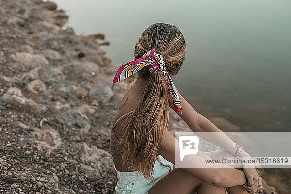 Rückansicht einer an einem Seeufer sitzenden jungen blonden Frau  Haare mit Tuch