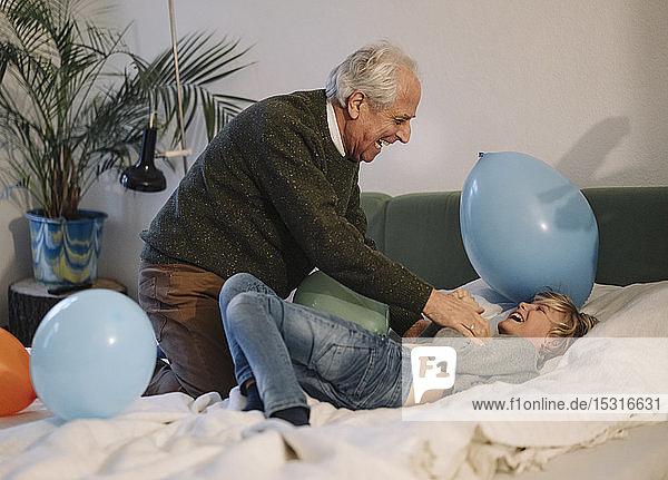 Glücklicher Großvater spielt mit seinem Enkel zu Hause im Bett