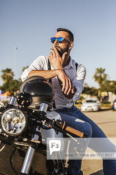 Portrait of bearded motorcyclist with mirrored sunglasses sitting on his motorbike smoking