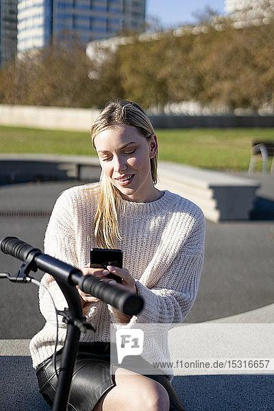 Porträt einer jungen Frau mit Kickroller  die bei Sonnenlicht mit einem Smartphone auf einer Bank sitzt