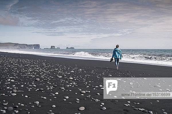 Young woman walking on barefoot on a lava beach in Iceland