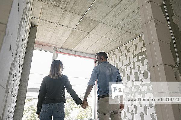 Glückliches Paar künftiger Eigentümer auf der Baustelle
