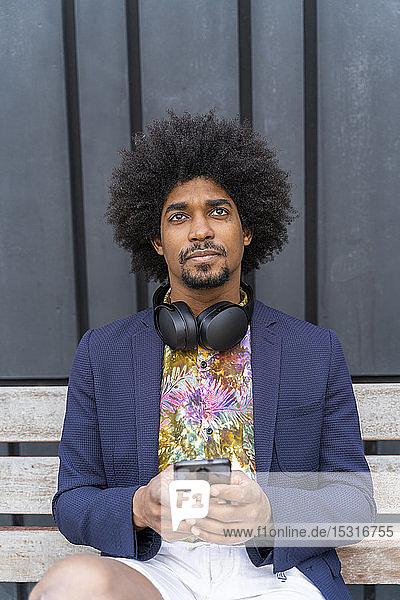 Stilvoller Mann mit Handy auf einer Bank sitzend