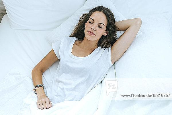 Junge Frau schläft zu Hause im Bett
