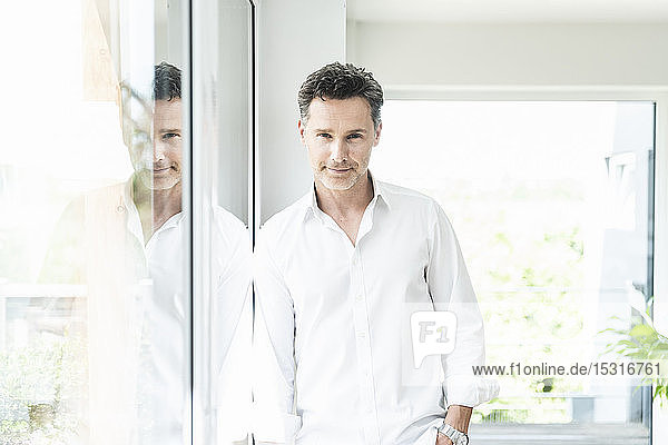 Serene man leaning on window at home