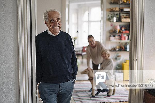 Glücklicher Großvater mit Frau und Enkel zu Hause im Hintergrund
