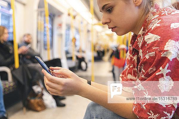 Junge Frau  die mit einem Smartphone im Zug reist