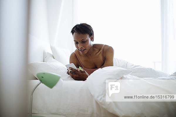 Woman lying in bed at home using cell phone
